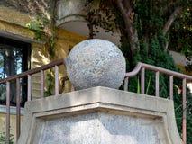 Stenbollen på sockeln smyckar hörnet av staketet som göras av betong och metall royaltyfria bilder