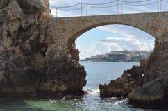 Stenbro av Cala Major Beach med en sikt av staden Palma de Mallorca, Spanien Arkivfoto