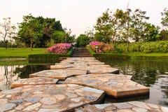 Stenbro i härlig trädgård Arkivfoton