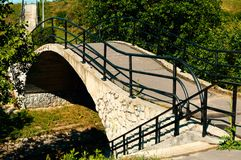 Stenbron över den lilla floden i staden parkerar royaltyfria foton