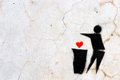 Stencil Graffiti of a heart thrown in a trash bin Stock Photo