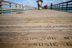 Stencilled letters on a wooden jetty in Florida. Old stencilled letters on a wooden jetty in Florida, USA, in a low angle view with fishermen visible in the stock image