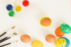 Stencils for painting Easter eggs, paints and brushes on a white background. Preparing for Easter. Copy space.