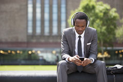 Stående av afrikansk amerikanaffärsmannen som utomhus lyssnar till musik med hörlurar Royaltyfria Foton