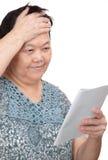 Stående av att le den höga kvinnan som läser en bok Arkivfoto