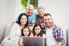Stående av att le den mång- utvecklingsfamiljen som använder bärbara datorn Royaltyfri Fotografi