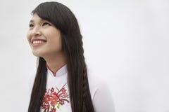 Stående av att le den unga kvinnan med långt hår som bär en traditionell klänning från Vietnam, studioskott Royaltyfri Bild