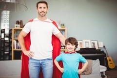 Stående av att le fadern och sonen i superherodräkt Royaltyfri Foto
