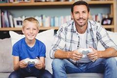 Stående av att le fadern och sonen som spelar videospelet Arkivbild