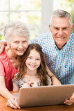 Stående av att le morföräldrar och sondottern som använder bärbara datorn Arkivbilder