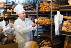 Stående av bagaren med nytt bröd som ler i bageri Arkivfoto