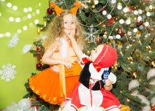 Stående av barnflickor i ekorrar för en dräkt runt om en dekorerad julgran Ungar på nytt år för ferie Arkivbild