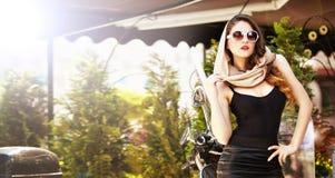 Stående av den attraktiva flickan för mode med sjaletten och solglasögon förutom en gammal sparkcykel Arkivbild
