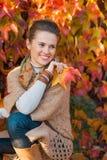 Stående av den eftertänksamma kvinnan med blad som är främsta av höstlövverk Arkivfoton