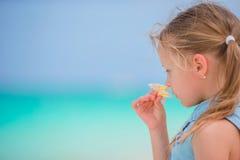 Stående av den förtjusande lilla flickan med blommafrangipanien på strandsommarsemester Royaltyfri Bild