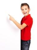 Stående av den gladlynt pojken som pekar på det vita banret Royaltyfri Bild
