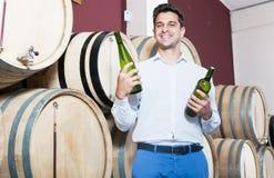 Stående av den gladlynta mankunden som har flaskan av vin Arkivbild