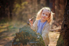 Stående av den gulliga lyckliga barnflickan som spelar med trädet i tidig vårskog Royaltyfri Foto
