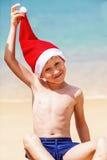 Stående av den gulliga pysen i jultomtenhatt Arkivbilder