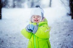 Stående av den gulliga pysen i vinterkläder med fallande snö Lura att spela och att le i naturförkylningdag Royaltyfri Fotografi