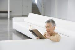 Stående av den höga kvinnaläseboken på soffan Royaltyfria Bilder