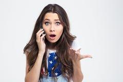 Stående av den häpna kvinnan som talar på telefonen Arkivbild
