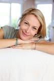 Stående av den härliga blonda kvinnabenägenheten på soffan Arkivbild
