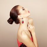 Stående av den härliga brunettkvinnan med örhänget. Perfekt makeu Arkivfoto