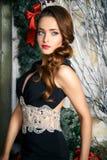 Stående av den härliga eleganta unga kvinnan i ursnygg aftonklänning över julbakgrund Arkivfoto
