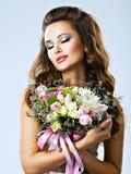 Stående av den härliga flickan med blommor i händer Arkivfoto
