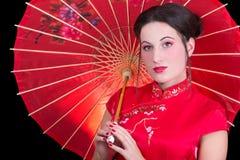Stående av den härliga geishaen i röd japansk klänning med paraplyet Arkivfoto