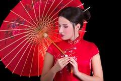 Stående av den härliga kvinnan i röd japansk klänning med paraplyet Arkivbild