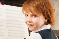 Stående av den härliga lilla flickan som spelar pianot Arkivbild
