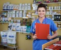 Stående av den härliga sjuksköterskan med mappen på veterinärkliniken Royaltyfri Fotografi