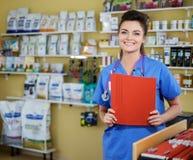 Stående av den härliga sjuksköterskan med mappen på veterinärkliniken Arkivbild