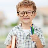 Stående av den härliga skolapojken som ser jätteglad det fria på Arkivfoton