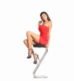 Stående av den härliga unga brunettkvinnan i stilfull röd klänning och pumps som sitter på stångstol Fotografering för Bildbyråer