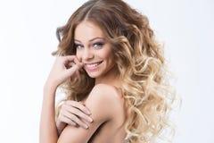 Stående av den härliga unga le flickan med frodigt krulla för hår Vård- och skönhet Royaltyfri Foto