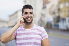 Stående av den härliga unga mannen som talar på den utomhus- telefonen Arkivfoto