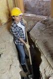 Stående av den kvinnliga arbetaren som gräver med skyffeln på konstruktionsplatsen Arkivfoton