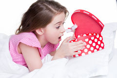 Stående av den lilla förvånade flickan med en gåva. Arkivfoto