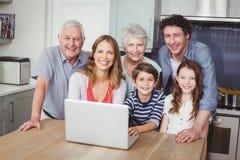 Stående av den lyckliga familjen som använder bärbara datorn i kök Arkivfoton