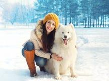 Stående av den lyckliga kvinnan med den vita Samoyedhunden utomhus Fotografering för Bildbyråer