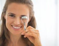 Stående av den lyckliga kvinnan som använder ögonfranshårrullen Arkivbild