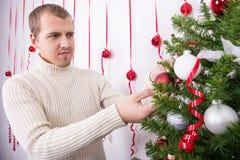 Stående av den lyckliga mannen som dekorerar julgranen Fotografering för Bildbyråer