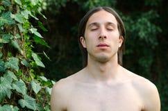Stående av den nakna mannen med stängda ögon som står i skog Royaltyfri Fotografi