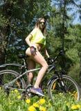 Stående av den nätta unga kvinnan med cykeln i en utomhus- parkera - Royaltyfri Fotografi