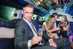 Stående av den säkra hållande champagneflöjten för ung man medan fr Royaltyfria Foton