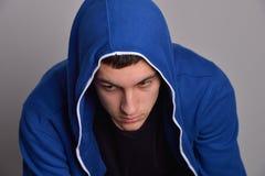 Stående av den säkra unga mannen som bär den blåa med huva tröjan Royaltyfri Fotografi