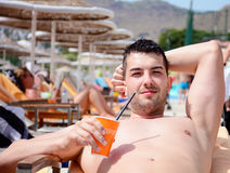Stående av den stiliga unga mannen som dricker fruktsaft på pölen Royaltyfria Bilder